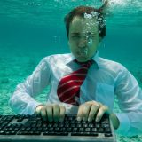 Young businessman with keyboard in formal clothes working underwater